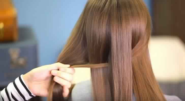 Elle divise les cheveux en deux parties égales, puis fait des tresses: Le résultat est digne d'un professionnel